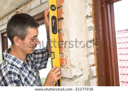 A construction man checking the level of a wall - stock photo