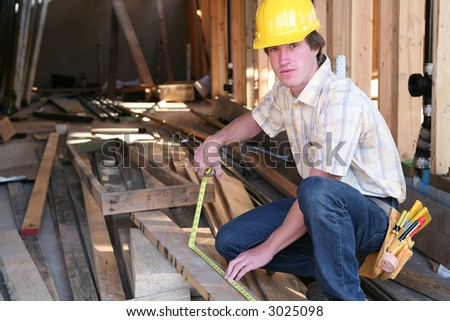 A construction man working building a home and measuring some wood - stock photo