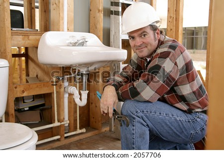 A construction plumber installing bathroom fixtures in a home under construction. - stock photo