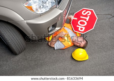 A construction road worker is injured by a car that didn't stop. - stock photo