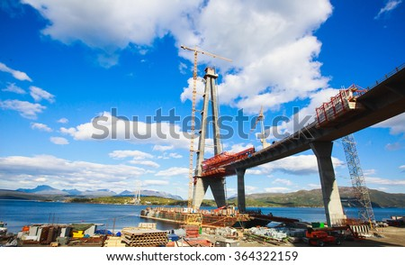A construction site of a giant bridge in Norway, over the fjord, lake, river  in a sunny summer day, high bridge under construction in progress, with a heavy vehicle and workers around - stock photo