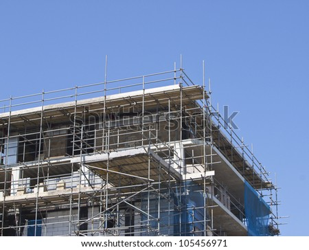 a construction site with scaffolding surrounding against wonderful blue sky