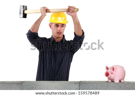 A construction worker about to open a piggy bank with a sledgehammer. - stock photo