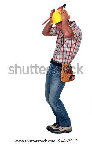 A construction worker afraid of a rodent. - stock photo