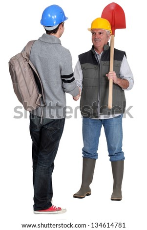 A construction worker and his apprentice. - stock photo