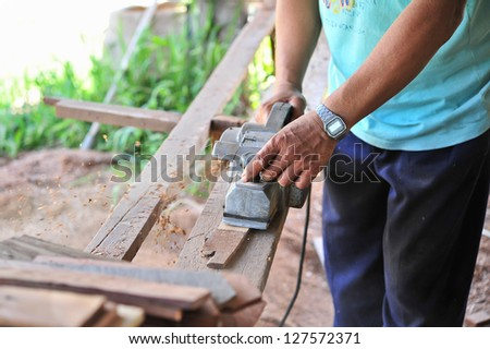 a construction worker and power tool while planing a piece of wood trim for a project.