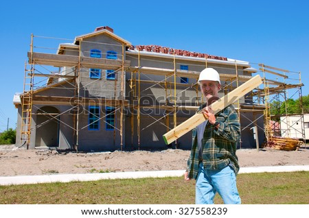 A construction worker contractor in a hard hat is walking through the front of a new house that is under construction - stock photo