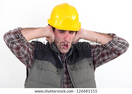 A construction worker covering his ears.