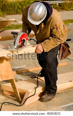 A construction worker cutting a piece of lumber with a circular saw to make a stair stringer - stock photo
