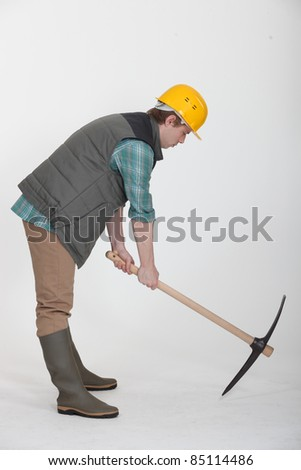 A construction worker digging with a pick axe. - stock photo