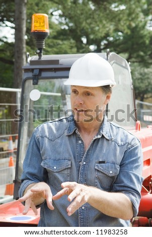 A construction worker discusses details of a job that he is working on. - stock photo