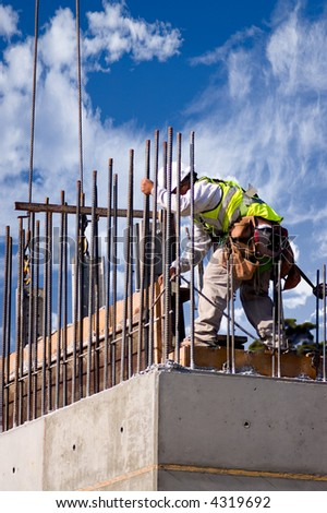 A construction worker guiding a section into place on a high concrete wall, shot against a cloudy sky. - stock photo