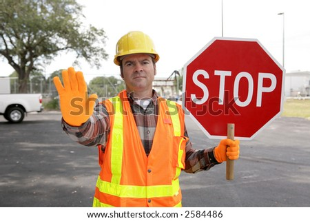 A construction worker holding a STOP sign and directing traffic. - stock photo
