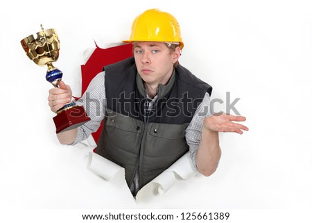 A construction worker holding a trophy cup. - stock photo