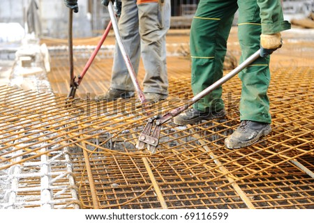 A construction worker hooking up iron beams - stock photo