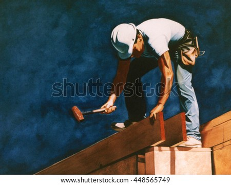 A construction worker, in a white construction han with a carpenters tool belt hammering a plank of wood - stock photo