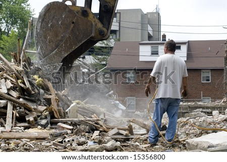 A construction worker inspects the scoop on a power shovel, amid the debris field of a partially-demolished building. - stock photo