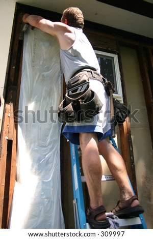A construction worker installing insulation to the wall of a house - stock photo