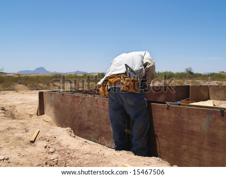 A construction worker is working on an excavation site.  He is bending down and looking at his work.  Horizontally framed shot.