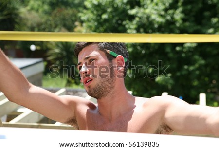 A construction worker measures with a rule in the sunshine - stock photo