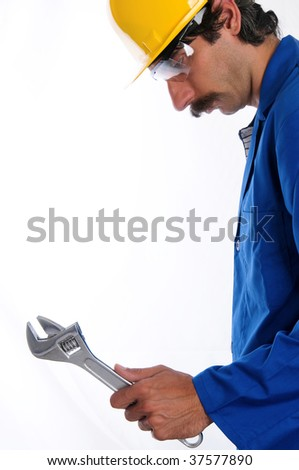 A construction worker/ mechanic wearing a blue jumpsuit, yellow hard hat and protective goggles, with a big wrench in his hand. - stock photo