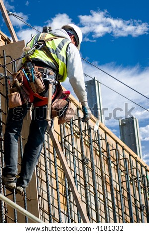 A construction worker on a high wall against a cloudy sky. - stock photo