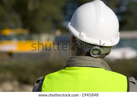A construction worker on site and dressed in safety clothing - stock photo
