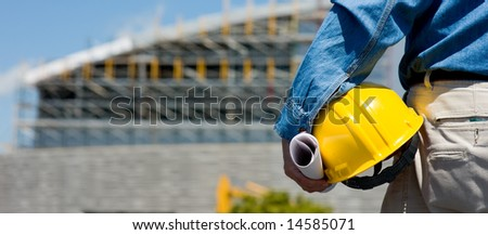 A construction worker or foreman at a construction site observing the progress of construction job or project, with copy space - stock photo