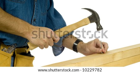 A construction worker or handy man driving a nail with a hammer in  two 2 x 4's