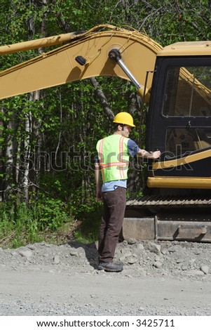 A construction worker prepares to climb into a utility excavator. - stock photo