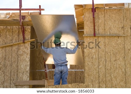 A construction worker raises a panel. - stock photo