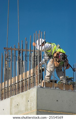 A construction worker releasing a concrete form from a wall. - stock photo