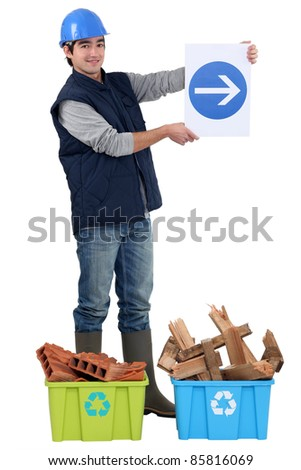 A construction worker showing the way to recycling. - stock photo