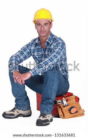 A construction worker sitting on his toolbox. - stock photo
