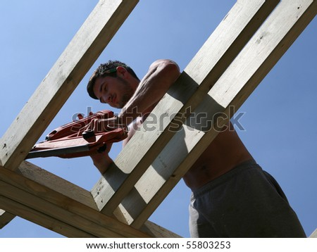 A construction worker uses a nail gun