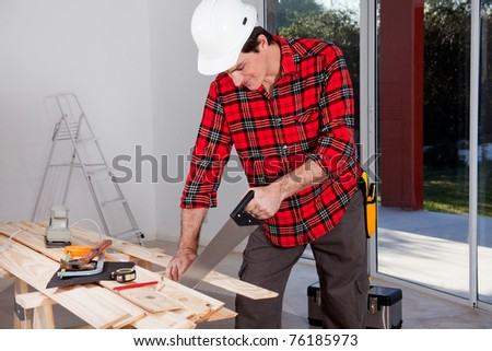 A construction worker using a hand wood saw while wearing a white safety helmet