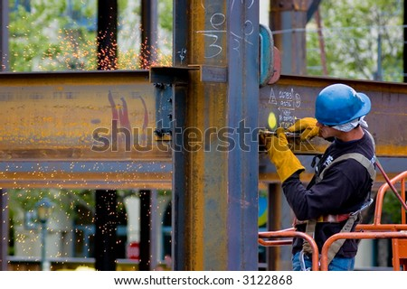A construction worker welding an iron beam - stock photo
