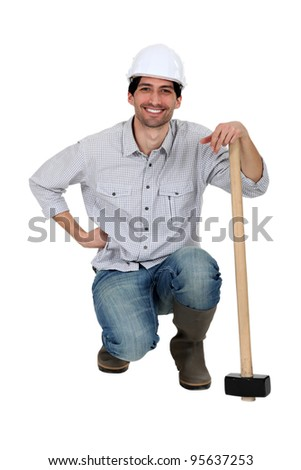 A construction worker with a sledgehammer. - stock photo