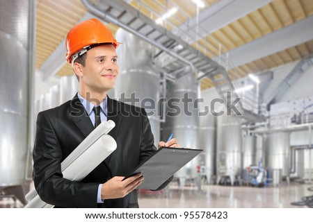 A construction worker with helmet holding blueprints and writing on a clipboard in a factory - stock photo