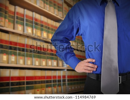 A consultant man is standing in front of a law library of books with copy space area. Use it for a attorney or education concept. - stock photo