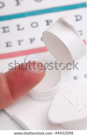 A contact lens sits on the end of a finger. Case and eye chart in background. Shallow dof, focus on contact lens and tip of finger. - stock photo