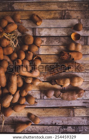 "A container full of ""tamarindos"". A very sour fruit grown in Puerto Rico. Nature's Laxative. - stock photo"