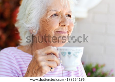 A content old woman holding a cup of tea - stock photo