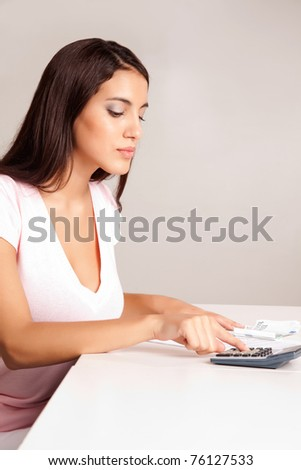 A content women calculating her finances at a desk with money and a calculator - stock photo