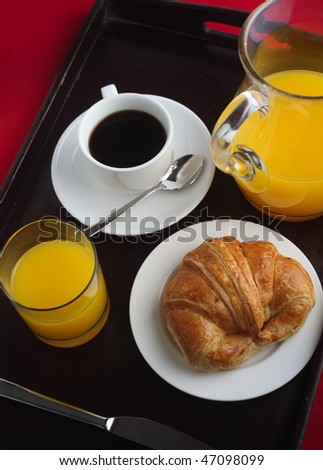A Continental breakfast on a tray over a red cloth, comprising orange juice, black coffee and a croissant - stock photo
