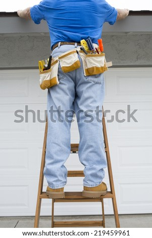 A contractor stands on a ladder and steadies himself by holding on to the edge of a home's roof. - stock photo