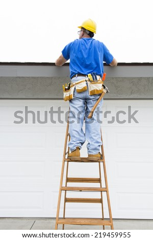 A contractor walks up a ladder to inspect the rook of a residential home during an overcast day - stock photo