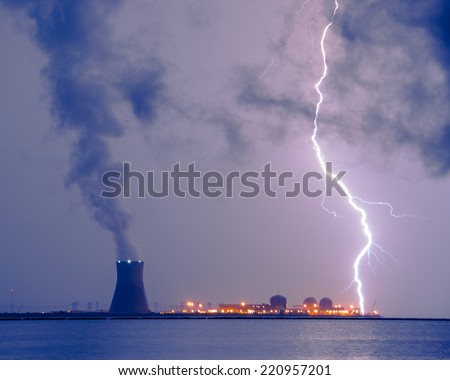 A contrast photograph of the power of mother nature and man-made energy; A lightning bolt striking the water in take area of a nuclear power plant. - stock photo