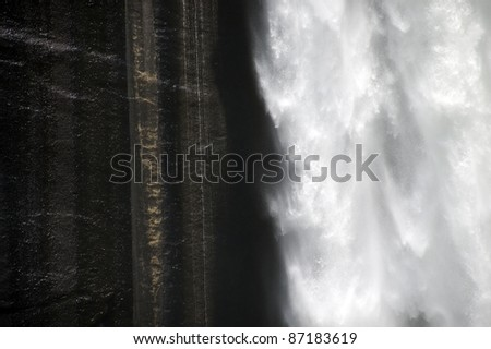 A contrasting image. Wet blackened granite contrasted with the bright white, oxygenated, icy water of the Merced River careening over Vernal Falls in Yosemite National Park. - stock photo