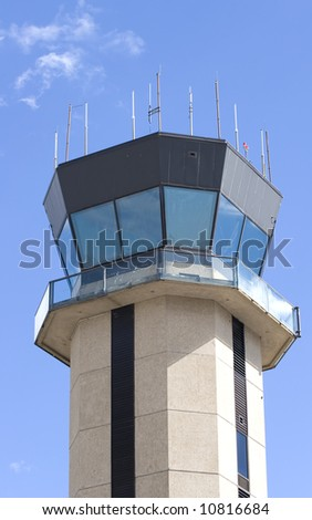 A control tower at a small regional airport against blue sky and clouds - stock photo